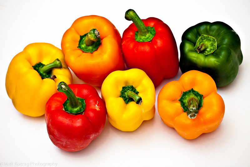 Bell peppers of red, orange, yellow and gree on a white background