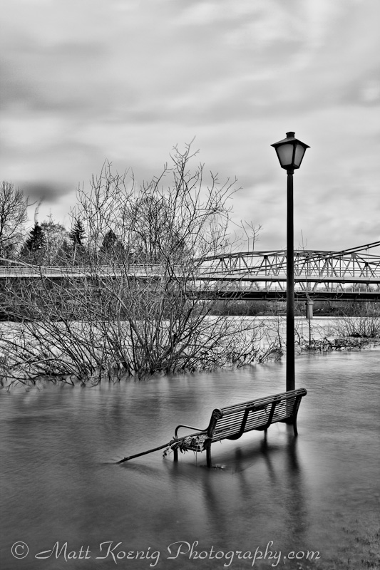 Park bench surrounded by flood waters